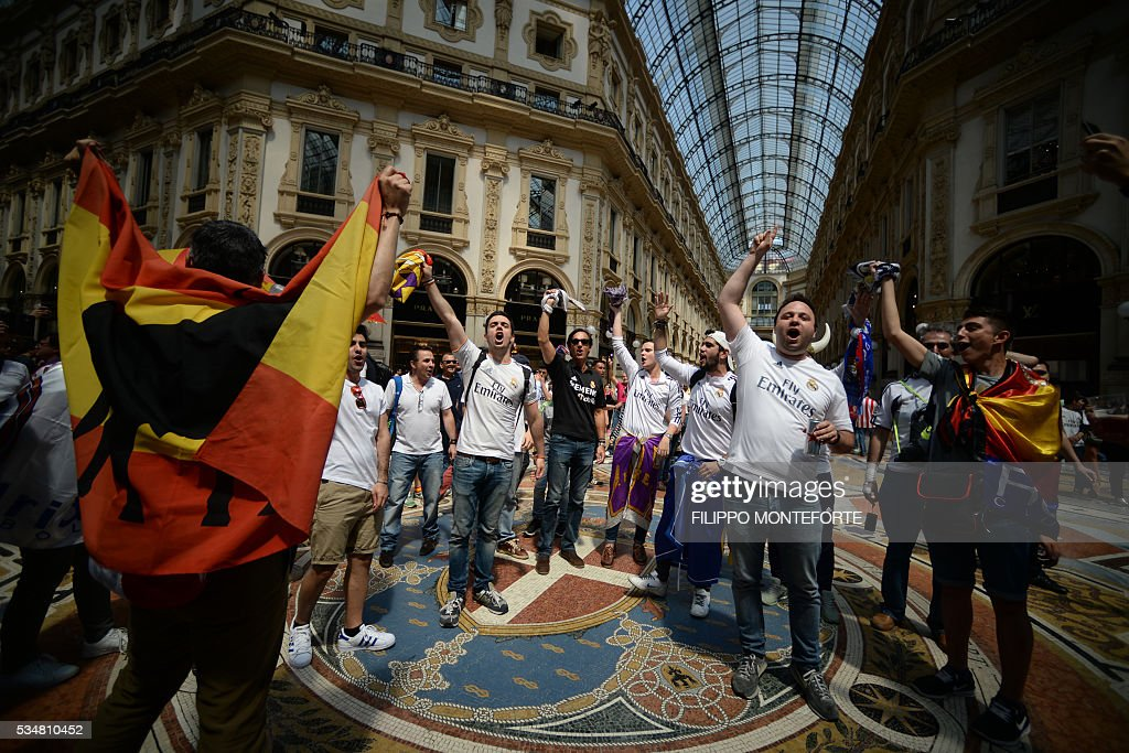 Supporters of the Real Madrid football club cheer their team inside the Galleria Vittorio Emanuele on the day of the Champions League final between Real Madrid and Atletico Madrid in Milan on May 28, 2016. AFP PHOTO / FILIPPO MONTEFORTE Record ten-time champions Real, who won the inaugural trophy in 1956, are gunning for their 11th title from European football's premier club event two years after a stunning comeback victory over Atletico in Lisbon secured 'La Decima'. / AFP / FILIPPO