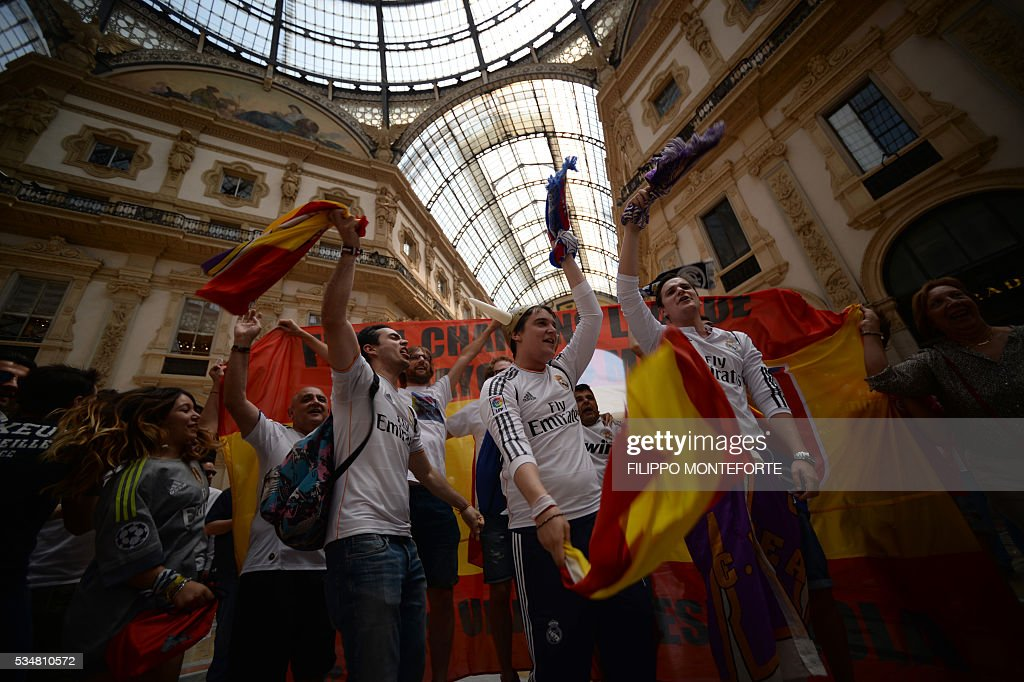Supporters of the Real Madrid football club cheer their team inside the Galleria Vittorio Emanuele on the day of the Champions League final between Real Madrid and Atletico Madrid in Milan on May 28, 2016. Record ten-time champions Real, who won the inaugural trophy in 1956, are gunning for their 11th title from European football's premier club event two years after a stunning comeback victory over Atletico in Lisbon secured 'La Decima'. / AFP / FILIPPO