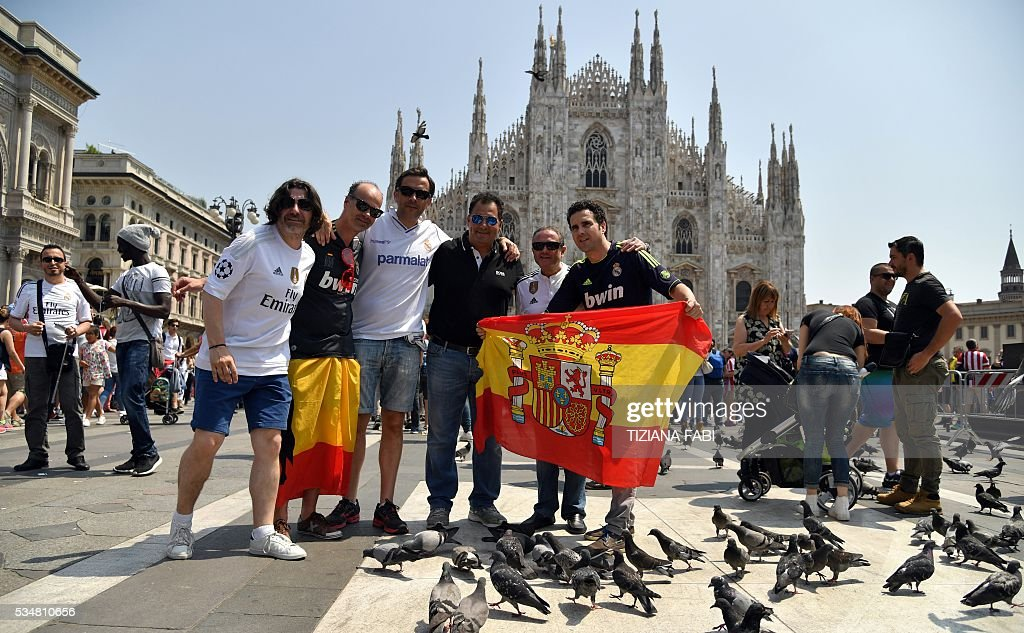 Supporters of the Real Madrid team pose with Spanish National flag in front of Milan's cathedral during a gather at the Piazza Duomo - Duomo Square in Milan on May 28, 2016 on the day of the Champions League final between Real Madrid and Atletico Madrid. Record ten-time champions Real, who won the inaugural trophy in 1956, are gunning for their 11th title from European football's premier club event two years after a stunning comeback victory over Atletico in Lisbon secured 'La Decima'. / AFP / TIZIANA