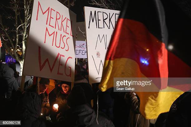 Supporters of the rightwing AfD political party hold signs that read 'Merkel must go' at a vigil near the Chancellery for victims of the recent...