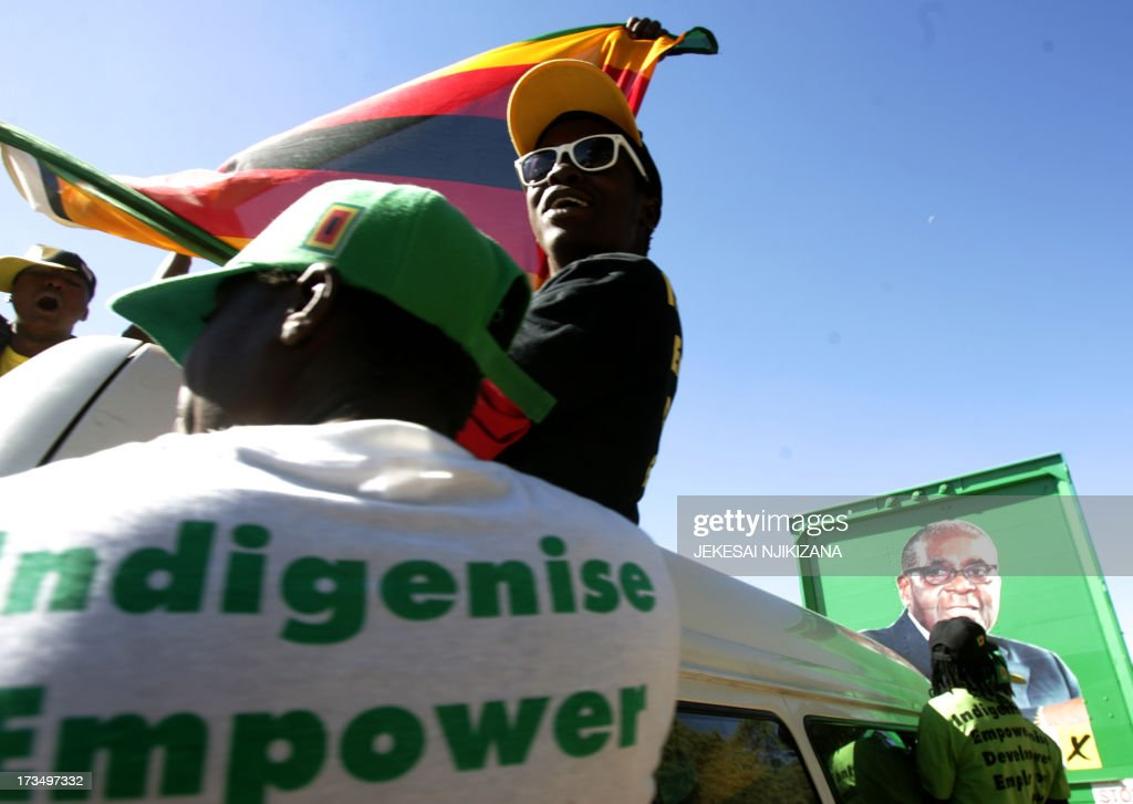 Supporters of the Robert Mugabe of the ZANU PF wave the country's flag during a party rally on July 15, 2013 addressed by the president in Marondera, Zimbabwe. AFP PHOTO/ Jekesai Njikizana.