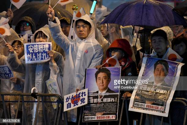 Supporters of the ruling Liberal Democratic Party display posters while waiting for Japan's Prime Minister Shinzo Abe to arrive for his last stumping...