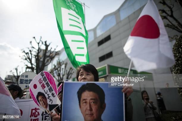 Supporters of the ruling Liberal Democratic Party hold portraits of Japan's Prime Minister Shinzo Abe during an election campaign in Saitama on...