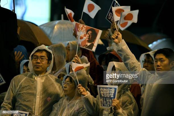 Supporters of the ruling Liberal Democratic Party wait for Japan's Prime Minister and Shinzo Abe to arrive for his last stumping tour for the October...