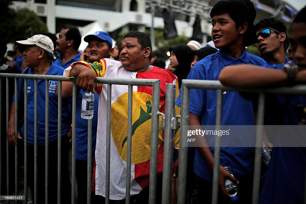 Supporters of the ruling National Front coalition, or Barisan Nasional, line up to enter the stadium in Bukit Jalil, a suburb of Kuala Lumpur, on April 6, 2013 before Malaysia's Prime Minister Najib Razak launches his coalition's election manifesto ahead of upcoming polls. Razak said on April 4 he is 'cautiously optimistic' of a 'big' win on election day if his party can overcome its internal woes. AFP PHOTO / MOHD RASFAN