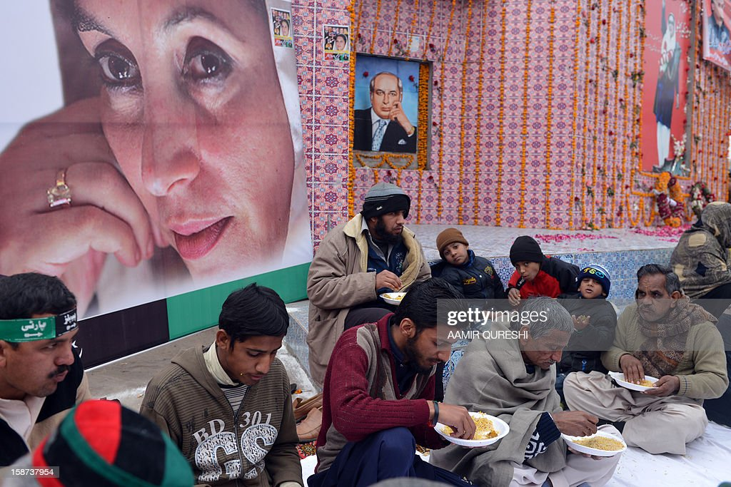 Supporters of the ruling Pakistan Peoples Party (PPP) eat communal food in front of portraits of former premier Benazir Bhutto (L) and her father and former prime minister Zulfikar Ali Bhutto (2nd L), at the site where Benazir was assassinated on her fifth death anniversary in Rawalpindi on December 27, 2012. Pakistan marks the fifth anniversary of the assassination of former prime minister Benazir Bhutto, with her son expected to launch his political career with a speech in the family's ancestral home town. Bhutto, twice elected prime minister, was killed in a gun and suicide attack after an election rally in Rawalpindi, the headquarters of Pakistan's army, on December 27, 2007. AFP PHOTO/Aamir QURESHI