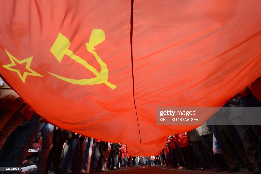 Supporters of the Russian Communist Party hold a giant flag as they take part in a rally against rising utility bills in Moscow on September 22 2012...