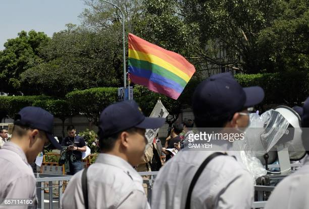 Supporters of the same sex rights display a flag in front of policemen outside the Judicial Yuan in Taipei on March 24 2017 Taiwan's constitutional...
