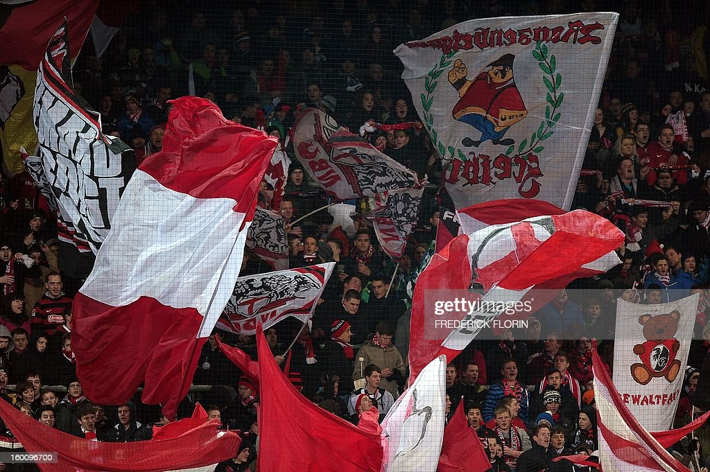 Supporters of the SC Freiburg wave flags before the German first division Bundesliga football match SC Freiburg vs Bayer 04 Leverkusen in Freiburg, southern Germany, on January 26, 2013.