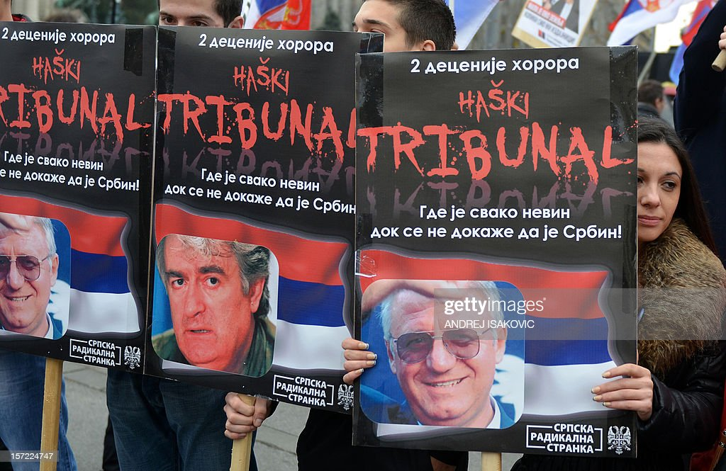 Supporters of the Serbian Radical Party (SRS) hold posters of party leader Vojislav Seselj (L and R) and Bosnian wartime leader Radovan Karadzic (C) on November 30, 2012 during a protest held in front of the Serbian Presidency in downtown Belgrade against the International Criminal Tribunal for the Former Yugoslavia (ICTY) court after it cleared ethnic Albanian former rebel chief Ramush Haradinaj of war crimes. Hundreds of demonstrators asked the authorities to give up their bid to become a member of the European Union.