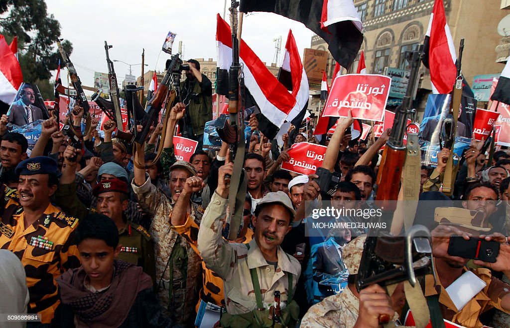 Supporters of the Shiite Huthi movement wave their national flag and banners reading in Arabic: 'our revolution continues' as they shout slogans during a rally commemorating the fifth anniversary of the 2011 Arab Spring uprising that toppled the then-president Ali Abdullah Saleh, on February 11, 2016 in the capital Sanaa. / AFP / MOHAMMED HUWAIS