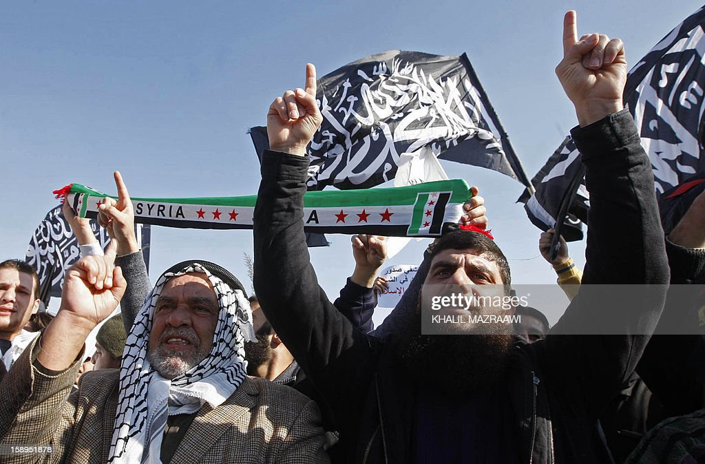 Supporters of the Sunni Islamist Hizb al-Tahrir (liberation party) wave their party flag and shout slogans alongside Syrian nationals living in Jordan during a protest in solidarity with Syrians, in front of the Syrian embassy, in Amman on January 4, 2013. The protesters shouted slogans against the US and United Nations-Arab League envoy Lakhdar Brahimi. AFP PHOTO/KHALIL MAZRAAWI