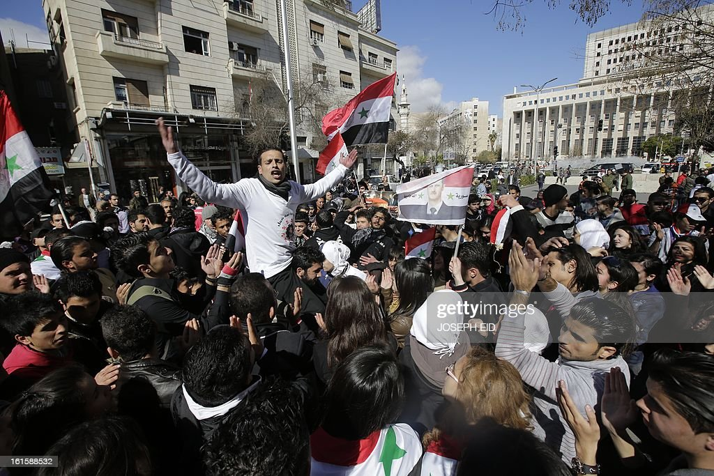 Supporters of the Syrian president wave national flags with his portaits in the streets of central Damascus in a small pro-regime rally on February 12, 2013 as rebels overran a military air base, according to the Syrian Observatory for Human Rights, a day after seizing control of Syria's largest dam in the north of the country. AFP PHOTO/JOSEPH EID
