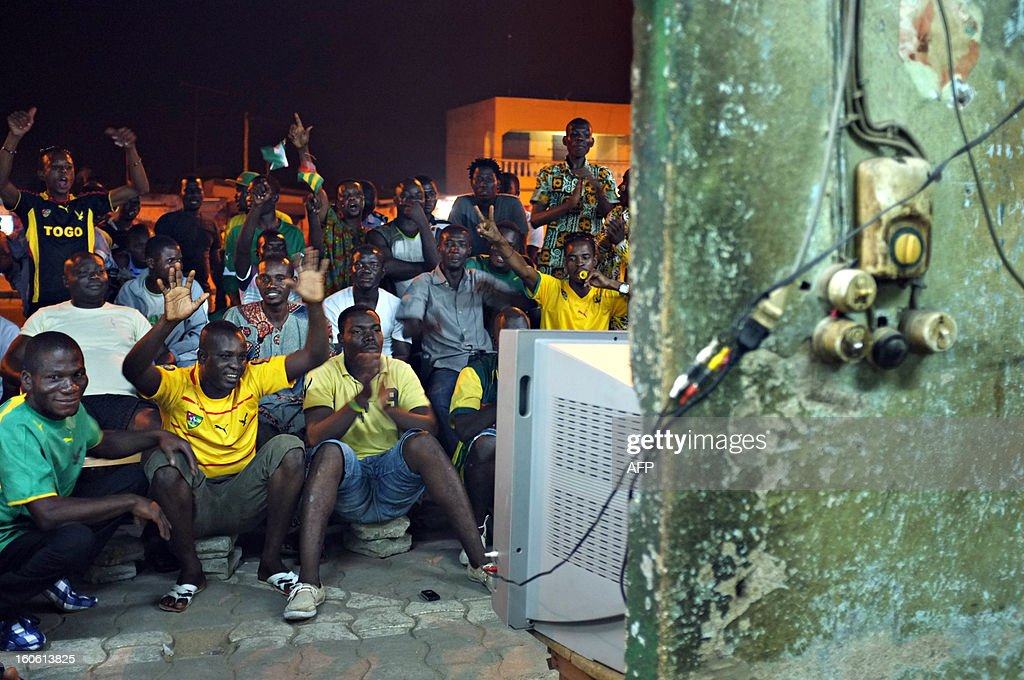 Supporters of the Togo football team watch on TV the African Cup of Nation 2013 quarter final football match between Burkina Faso and Togo, in Lome, on February 3, 2013. Burkina Faso qualified for the semi-finals of the 2013 Africa Cup of Nations Sunday by pipping Togo 1-0 after extra time. AFP PHOTO / Daniel Hayduk