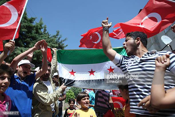 Supporters of the Turkish prime minister wave Turkey's national flag and the old Syrian flag now used by the opposition to the regime of the Syrian...