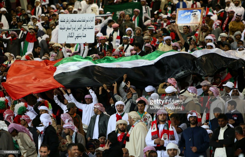 Supporters of the United Arab Emirates (UAE)' national football team wave a giant flag prior the start of the Gulf Cup's final football match between UAE and Iraq on January 18, 2013 in Manama . AFP PHOTO/MARWAN NAAMANI