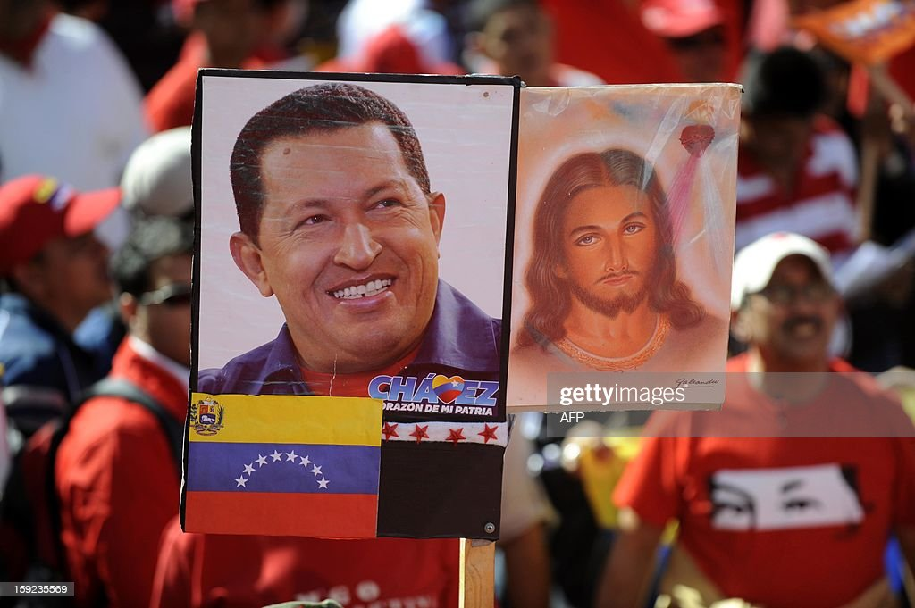 Supporters of the Venezuelan President Hugo Chavez show portraits of Chavez and Jesus Christ outside Miraflores Presidential Palace during a meeting in Caracas on January 10, 2013. With Chavez ailing and absent, Venezuela's leftist government launches a new presidential term with a display of popular support on the day he was to be inaugurated. The Supreme Court cleared the cancer-stricken president to indefinitely postpone his re-inauguration and said his existing administration could remain in office until he is well enough to take the oath.AFP PHOTO/Leo RAMIREZ
