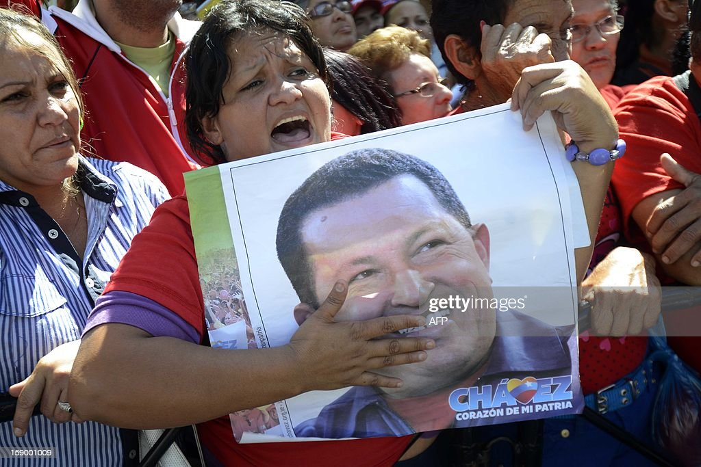 Supporters of the Venezuelan President Hugo Chavez shut slogans holding a poster of him outside of the National Assembly in Caracas on January 5, 2013. Venezuelan lawmakers gathered Saturday for a key leadership vote as President Hugo Chavez's battle with cancer appeared almost certain to delay his swearing-in for a new six year term. Hundreds of supporters chanted for Chavez outside the National Assembly in a show of unity during a period of high uncertainty about the country's future. AFP PHOTO/Leo Ramirez