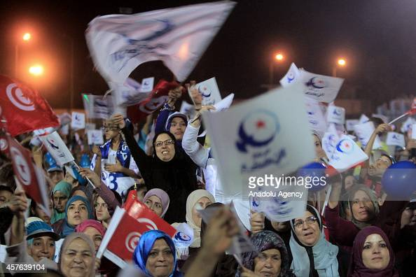 Supporters of Tunisian Ennahda Party hold Tunisian national flag party's flags and shout slogans as the founder of Ennahda movement Rashid...