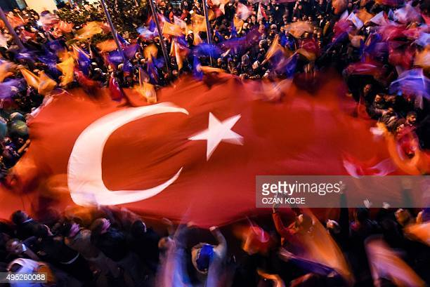 Supporters of Turkey's Justice and Development Party wave a giant Turkish flag as they celebrate in Istanbul after the first results in the country's...