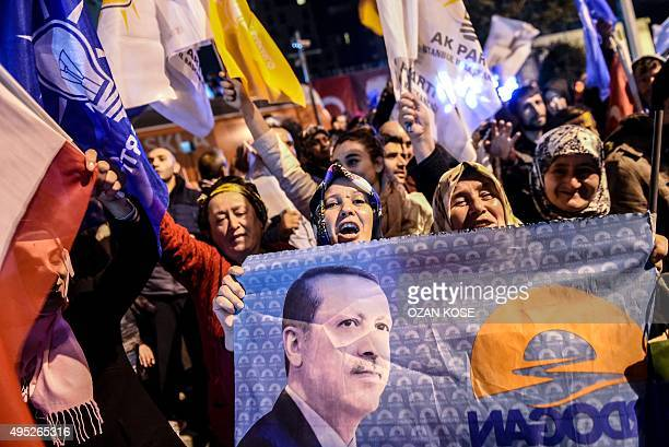 Supporters of Turkey's Justice and Development Party wave party flags and hold a flag with a portrait of Turkish President Recep Tayyip Erdogan as...