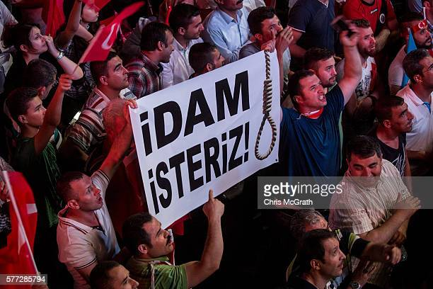 Supporters of Turkish President Recep Tayyip Erdogan hold up a sign saying ' We want to execute' while attending a rally in Kizilay Square on July 18...