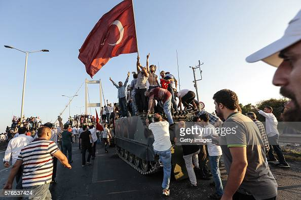 Supporters of Turkish President Recep Tayyip Erdogan wave flags as they capture a Turkish Army APC after soldiers involved in the coup attempt have...