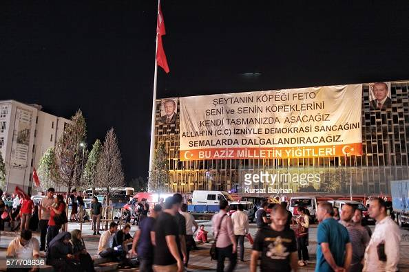Supporters of Turkish President Tayyip Erdogan gathers as a giant sign hangs on Ataturk Cultural Centers as read in Turkish 'FETO Satan's dog we'll...