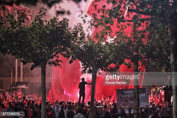 Supporters of Turkish President Tayyip Erdogan light flares and wave Turkish flags as they gather in Istanbul's central Taksim Square on July 19 2016...