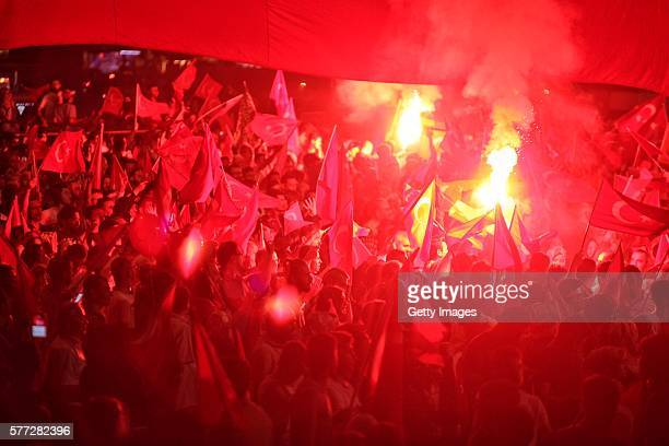 Supporters of Turkish President Tayyip Erdogan light flares as they gather in Istanbul's central Taksim Square on July 18 2016 in Istanbul Turkey...