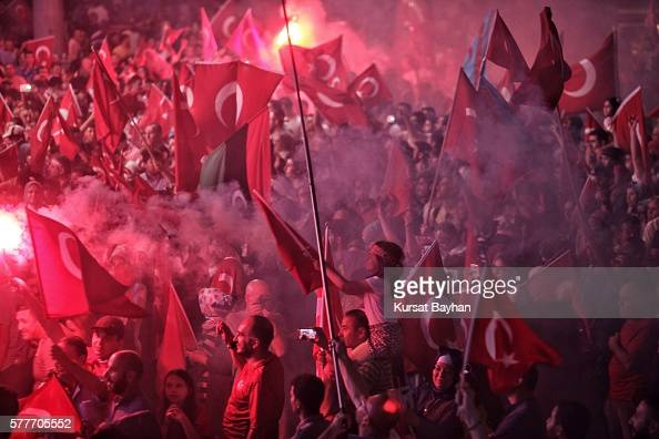 Supporters of Turkish President Tayyip Erdogan light frames and wave Turkish flags as they gather in Istanbul's central Taksim Square on July 19 2016...