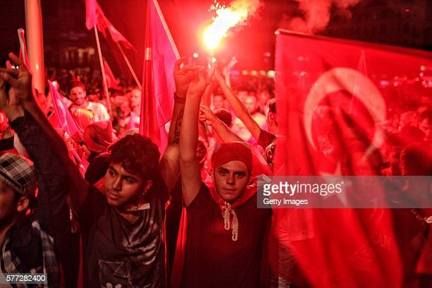 Supporters of Turkish President Tayyip Erdogan wave flags and light flares as they gather in Istanbul's central Taksim Square on July 18 2016 in...