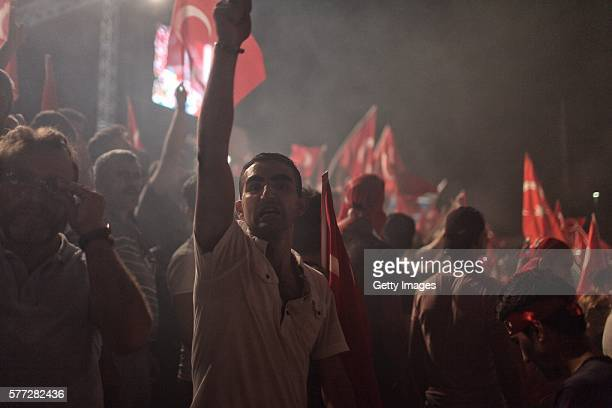 Supporters of Turkish President Tayyip Erdogan wave flags as they gather in Istanbul's central Taksim Square on July 18 2016 in Istanbul Turkey Clean...