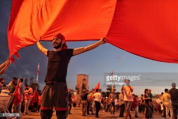 Supporters of Turkish President Tayyip Erdogan wave Turkish flags as they gather in Istanbul's central Taksim Square on July 18 2016 in Istanbul...