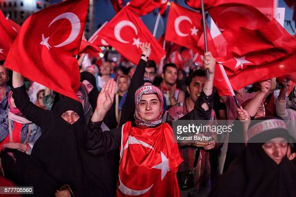 Supporters of Turkish President Tayyip Erdogan wave Turkish flags as they gather in Istanbul's central Taksim Square on July 19 2016 in Istanbul...
