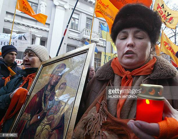 Supporters of Ukrainian opposition leader Victor Yushchenko carry icons and candles outside the Supreme court in Kiev 03 December 2004 The Supreme...