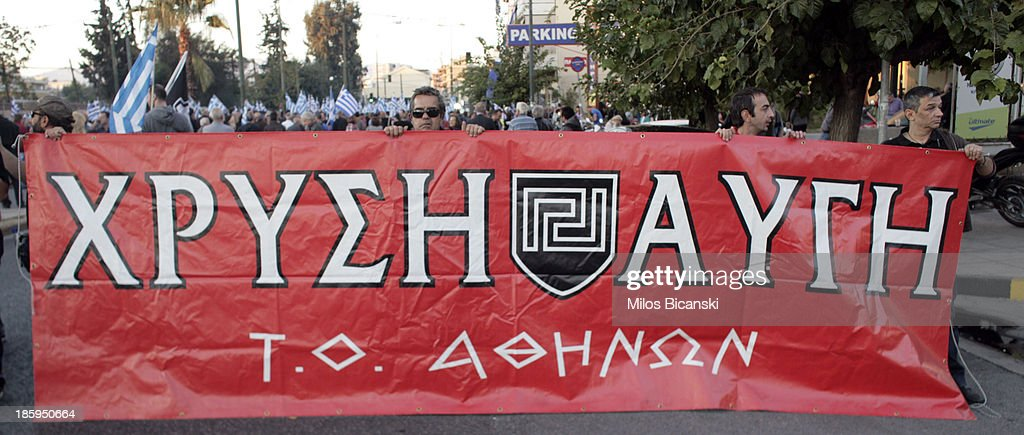 Supporters of ultra nationalist party Golden Dawn hold a banner as they demonstrate on October 26, 2013 in Athens, Greece. Members of the far right party Golden Dawn protest against the indictment of several Golden Dawn members and their leader Nikos Michaloliakos in a government crackdown. Some 2,000 neo-Nazi supporters gathered near Golden Dawn offices in central Athens.