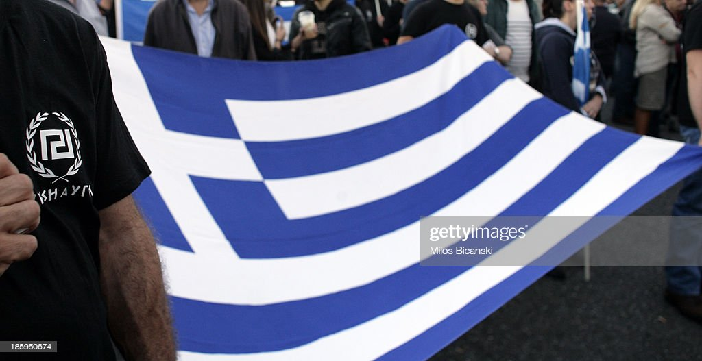 Supporters of ultra nationalist party Golden Dawn hold a Greek flag and shout slogans as they demonstrate on October 26, 2013 in Athens, Greece. Members of the far right party Golden Dawn protest against the indictment of several Golden Dawn members and their leader Nikos Michaloliakos in a government crackdown. Some 2,000 neo-Nazi supporters gathered near Golden Dawn offices in central Athens.