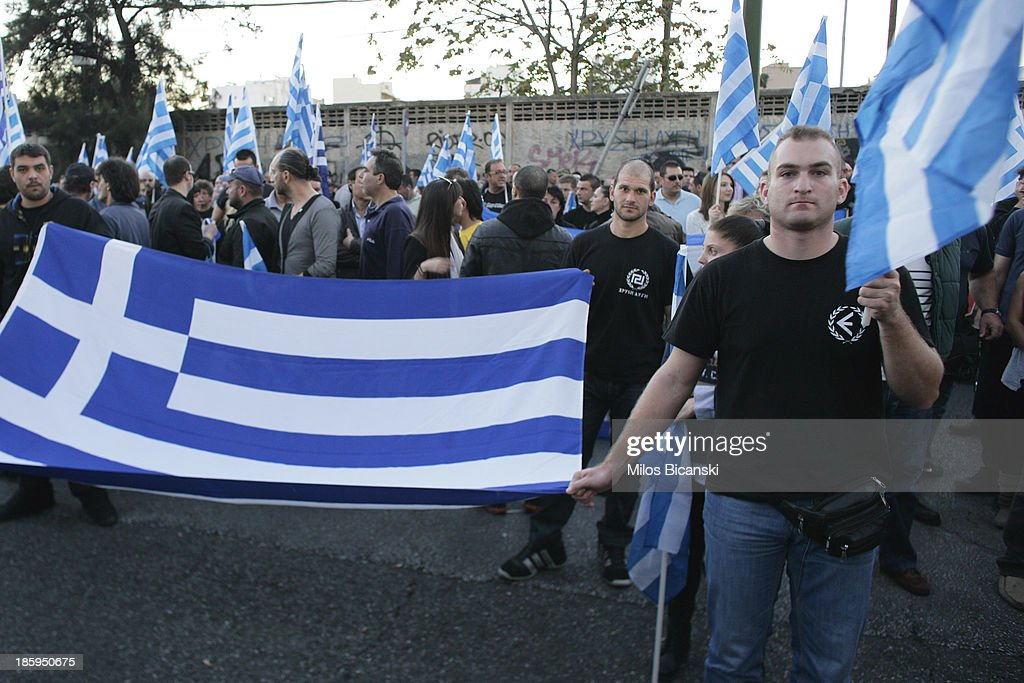 Supporters of ultra nationalist party Golden Dawn hold Greek flags as they demonstrate on October 26, 2013 in Athens, Greece. Members of the far right party Golden Dawn protest against the indictment of several Golden Dawn members and their leader Nikos Michaloliakos in a government crackdown. Some 2,000 neo-Nazi supporters gathered near Golden Dawn offices in central Athens.