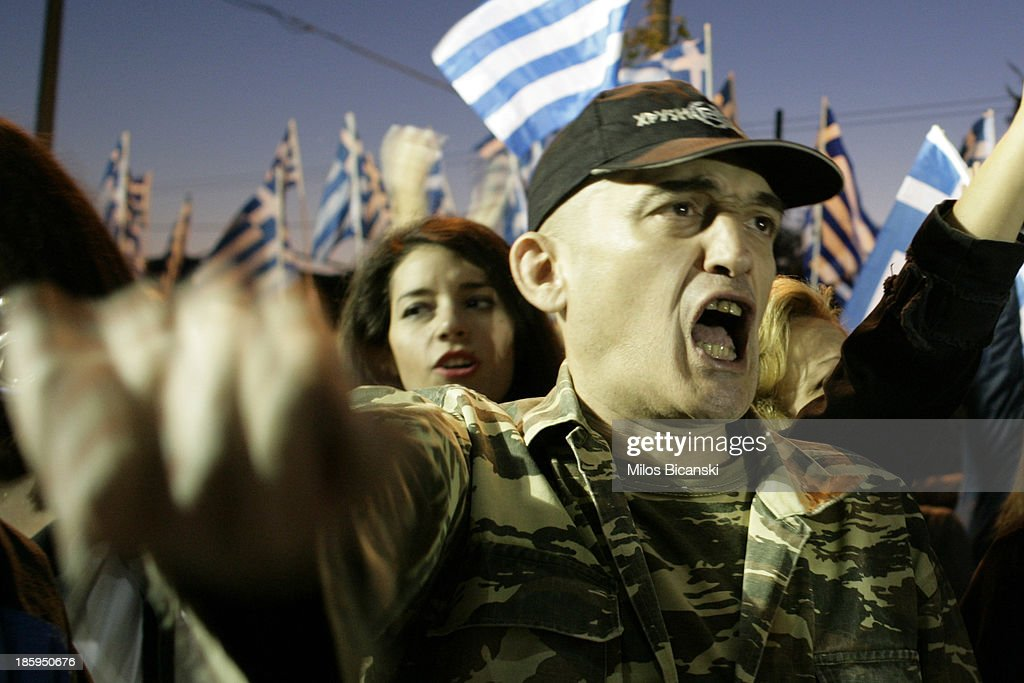 Supporters of ultra nationalist party Golden Dawn hold Greek flags and shout slogans as they demonstrate on October 26, 2013 in Athens, Greece. Members of the far right party Golden Dawn protest against the indictment of several Golden Dawn members and their leader Nikos Michaloliakos in a government crackdown. Some 2,000 neo-Nazi supporters gathered near Golden Dawn offices in central Athens.