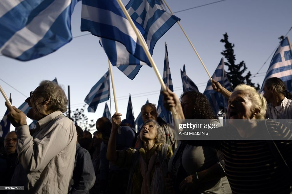 Supporters of ultra nationalist party Golden Dawn wave Greek flags and shout slogans as they demonstrate on October 26, 2013. Greek leftists and members of the neo-Nazi party Golden Dawn faced off in Athens on Saturday over a protest organised against the indictment of several Golden Dawn members in a government crackdown. Hundreds of leftist protesters and some 2,000 neo-Nazi supporters gathered near Golden Dawn offices in central Athens, an AFP reporter on the scene said.