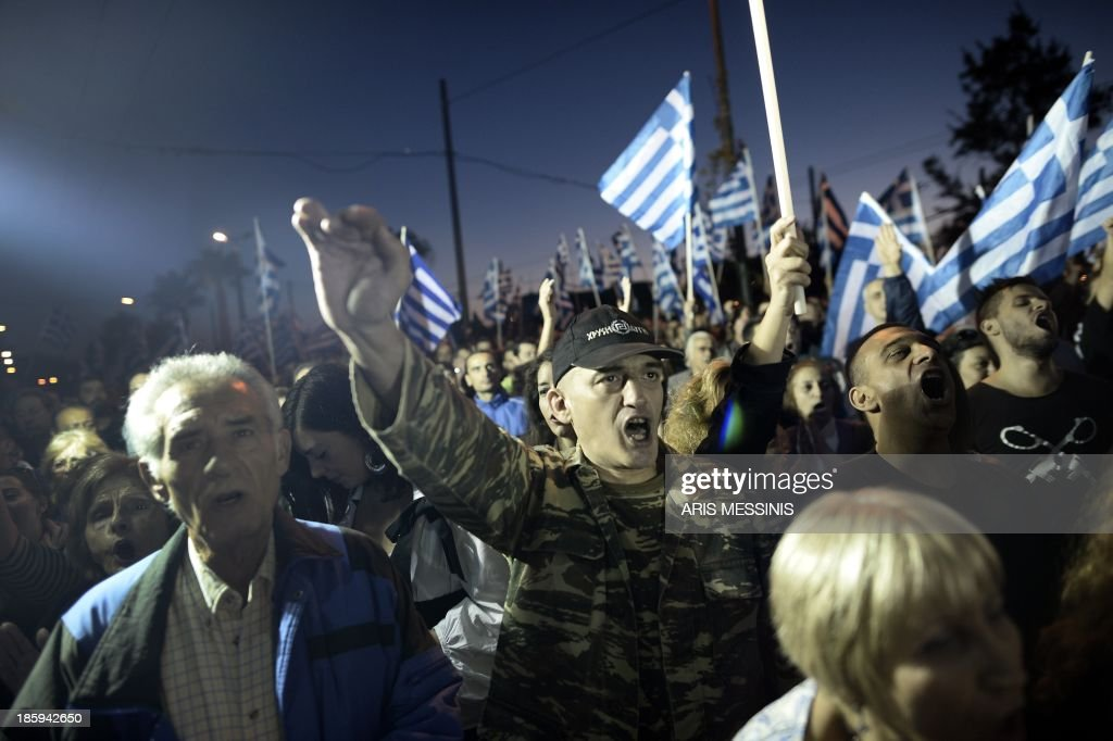 Supporters of ultra nationalist party Golden Dawn wave Greek flags and shout slogans as they demonstrate on October 26, 2013 in Athens. Greek leftists and members of the neo-Nazi party Golden Dawn faced off in Athens on Saturday over a protest organised against the indictment of several Golden Dawn members in a government crackdown. Hundreds of leftist protesters and some 2,000 neo-Nazi supporters gathered near Golden Dawn offices in central Athens, an AFP reporter on the scene said. AFP PHOTO / ARIS MESSINIS