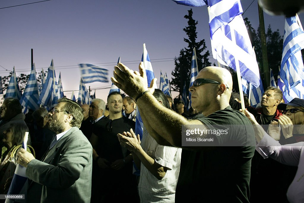 Supporters of ultra nationalist party Golden Dawn wave Greek flags and shout slogans as they demonstrate on October 26, 2013 in Athens, Greece. Members of the far right party Golden Dawn protest against the indictment of several Golden Dawn members and their leader Nikos Michaloliakos in a government crackdown. Some 2,000 neo-Nazi supporters gathered near Golden Dawn offices in central Athens.