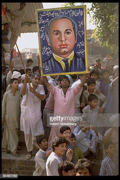 Supporters of unseen Pakistan People's Party cand Benzair Bhutto hold up picture of her father Zulfikar ali Bhutto