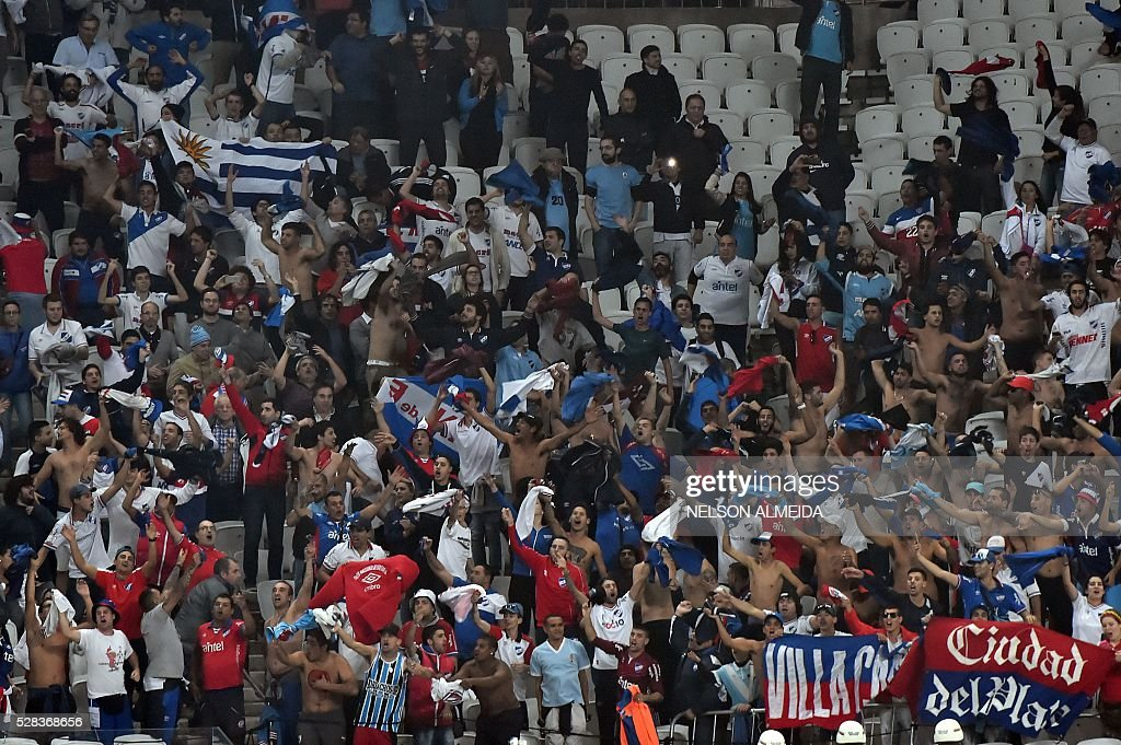 Supporters of Uruguay's Nacional cheer their team during the 2016 Copa Libertadores football match against Brazils Corinthians at Arena Corinthians stadium, in Sao Paulo, Brazil, on May 4, 2016. / AFP / NELSON