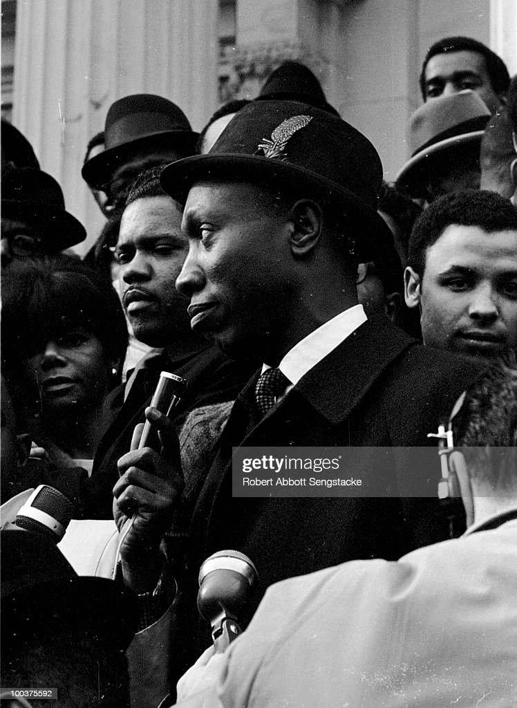 Supporters of US Congressman Adam Clayton Powell, Jr. gather on the Capitol steps to protest his having been stripped of the chairmanship of the Education and Labor Committee, January 1967. This view shows an unidentified supporter being interviewed by the media.
