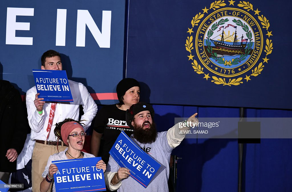 Supporters of US Democratic presidential candidate Bernie Sanders cheer as they watch the poll result on televison before a primary night rally in Concord, New Hampshire, on February 9, 2016. Self-described democratic socialist Bernie Sanders and political novice Donald Trump won New Hampshire's presidential primaries, US media projected, turning the American political establishment on its head early in the long nominations battle. / AFP / Jewel Samad