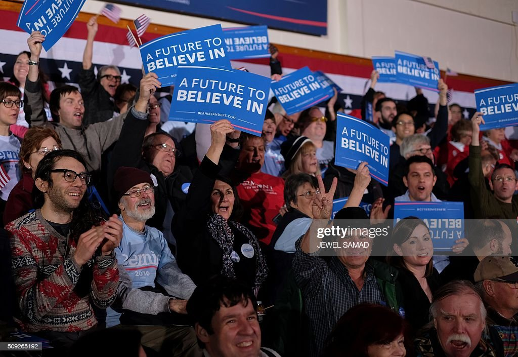 Supporters of US Democratic presidential candidate Bernie Sanders cheer watching the result on television as they arrive for primary night rally in Concord, New Hampshire, on February 9, 2016. / AFP / Jewel Samad