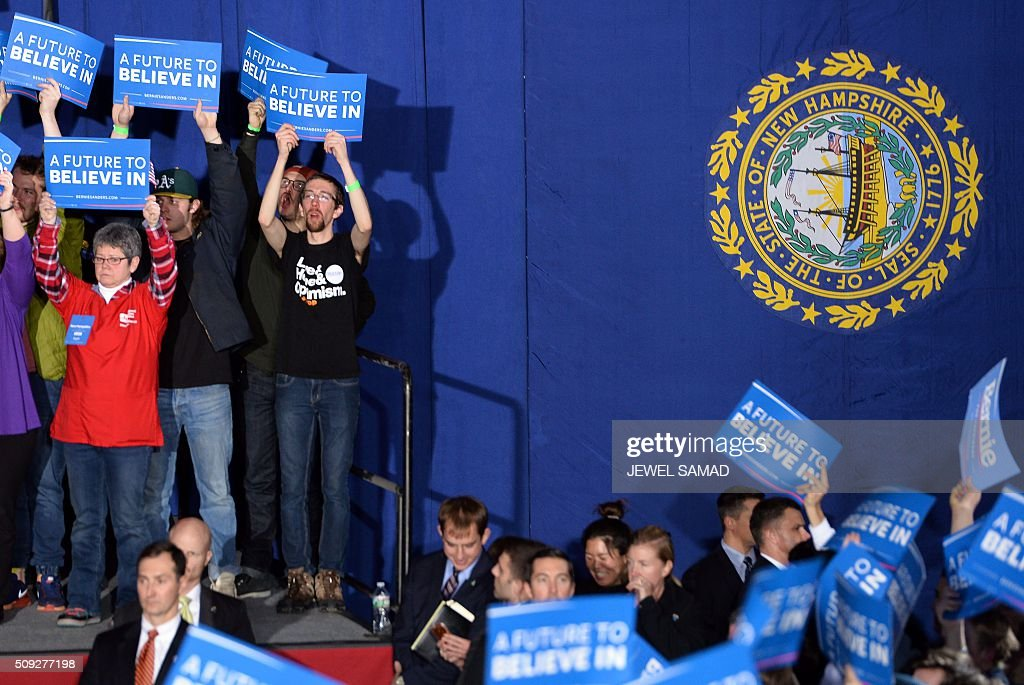 Supporters of US Democratic presidential candidate Bernie Sanders cheer during the primary night rally in Concord, New Hampshire, on February 9, 2016. Self-described democratic socialist Bernie Sanders and political novice Donald Trump won New Hampshire's presidential primaries Tuesday, US media projected, turning the American political establishment on its head early in the long nominations battle. / AFP / JEWEL SAMAD