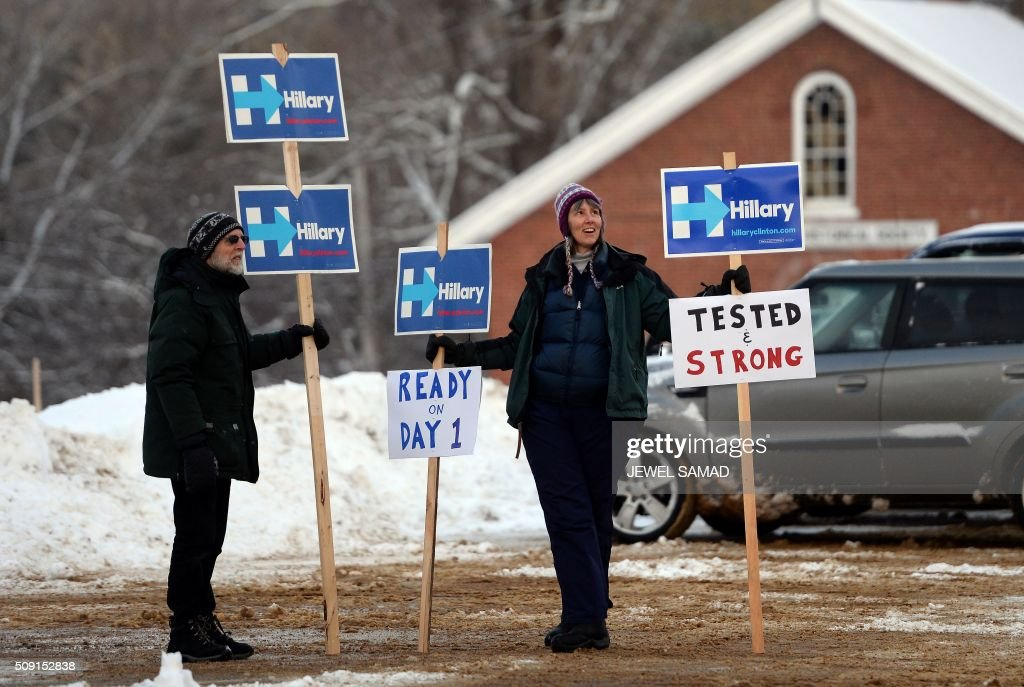 Supporters of US Republican presidential candidate Hillary Clinton display campaign posters outside the town hall as local residents vote for the first US presidential primary in Canterbury, New Hampshire, on February 9, 2016. New Hampshire began voting on February 9 in the first US presidential primary with Republican Donald Trump calling on supporters to propel him to victory and Democrat Bernie Sanders primed to upstage Hillary Clinton. The northeastern state, home to just 1.3 million people, sets the tone for the primaries and could shake out a crowded Republican field of candidates pitting Trump and arch-conservative Senator Ted Cruz against more establishment candidates led by Senator Marco Rubio. SAMAD